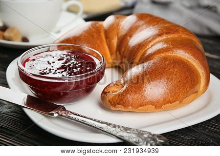 Plate with fresh tasty crescent roll and jam on wooden table, closeup