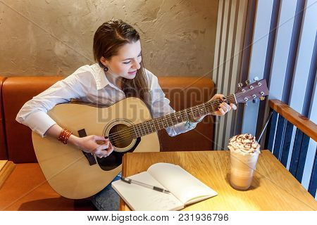Young Smiling Hipster Woman Sitting Playing Guitar And Write A Song At Cafe. Girl Learning To Play M