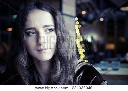 Girl Sitting In A Cafe. She Has Big Brown Eyes And Nice Brown Long Hair. Wearing A Brown Silk Blouse