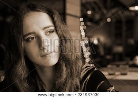 Lonely Handsome Girl Is Sitting In The Cafe. She Has Big Brown Eyes And Nice Brown Long Hair. Wearin
