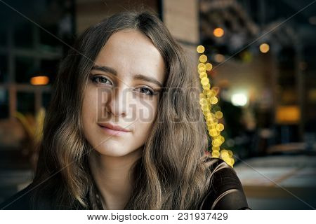 Pretty Girl Is Sitting In The Cafe. She Has Big Brown Romantic Eyes. With Nice Brown Long Hair. Wear