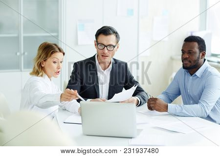 Confident businesswoman pointing at laptop display and explaining dollar fluctuations while making presentation for cilleagues at working meeting