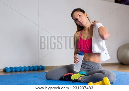 Restful girl in sportswear sitting on mat with towel on her shoulder and long plastic container with water in hand
