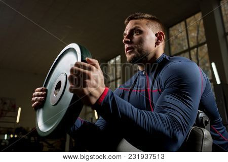 Muscular athlete holding heavy iron disk in front of him during weightlifting workout