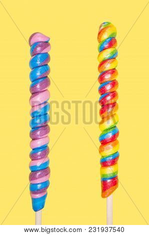 Two Long Colorful Lollipops On Yellow Background.