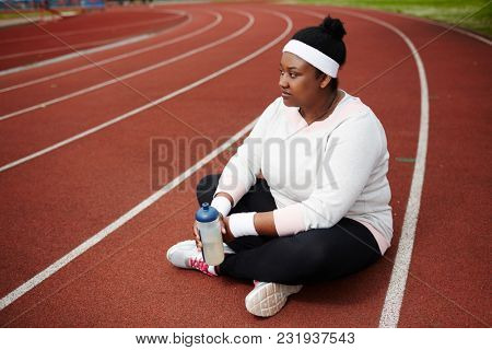 Young restful woman in sweatshirt, leggins and headband holding bottle of water and having break between workouts