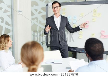 Elegant businessman pointing at whiteboard and explaining new business trends to colleagues at briefing