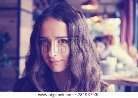 Pretty Looking Girl In A Cafe. With Big Brown Beautiful Eyes. With Nice Brown Long Hair. Wearing A B