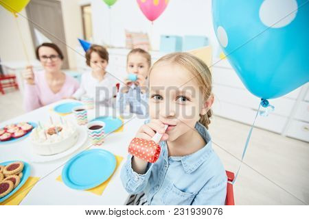 Happy cute girl with whistle looking at camera while sitting by festive table on background of her groupmates and teacher