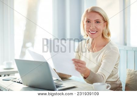 Happy mature businesswoman with toothy smile looking through papers in office