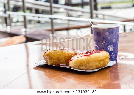 Donuts Whith Jam On Paper Plate And Coffee From Street Cafe. Selective Focus