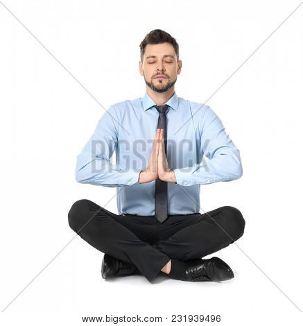 Young businessman meditating on white background