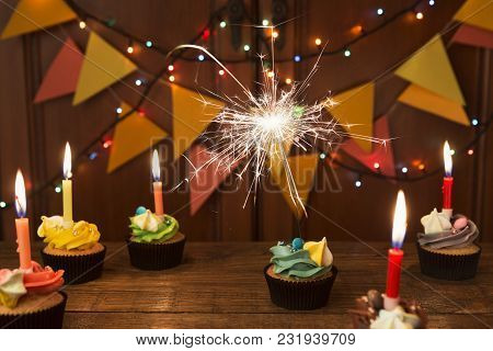 Chocolate Cupcakes With Colourful Icing And Candles Against Festive Background With Garland. Card Mo