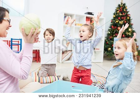 Ecstatic kids with raised hands looking at their teacher holding cabbage and describing it