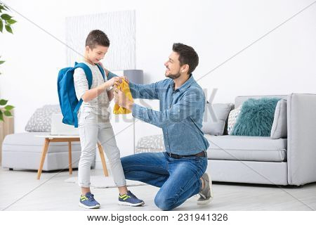 Young man helping his son get ready for school