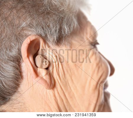 Senior woman with hearing aid on white background