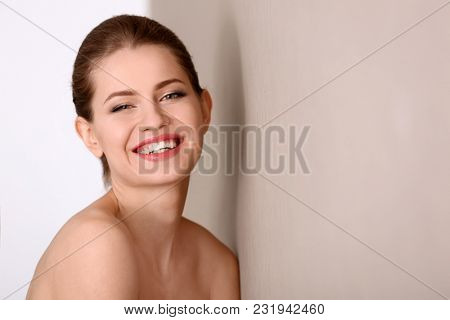 Portrait of beautiful young woman with soft skin after applying cream on light background