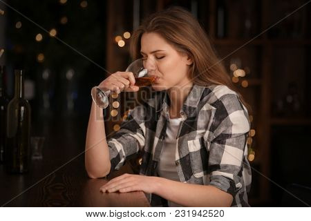 Young woman drinking wine in bar. Alcoholism problem