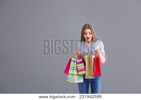 Emotional young woman looking inside of shopping bag on grey background