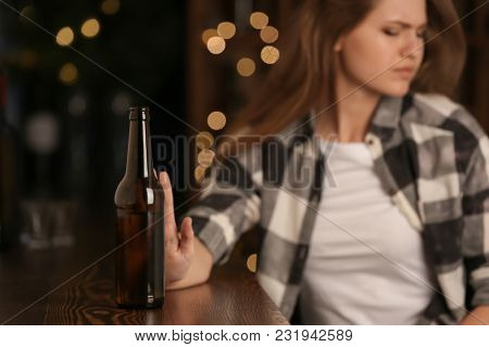 Young woman rejecting bottle of drink in bar. Alcoholism problem