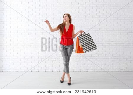 Beautiful young woman with shopping bags against brick wall