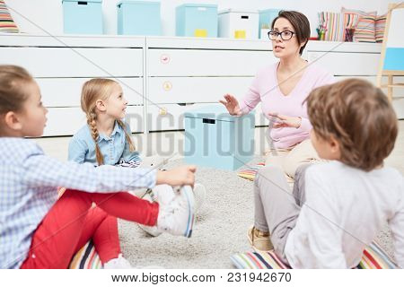 Young teacher explaining rules of game to group of elementary pupils in kindergarten