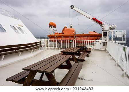 Wooden Benches And Orange Lifeboat On A Deck Of A White Ferry In Bad Cloudy Weather