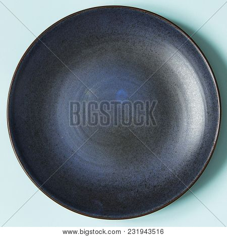 Empty Ceramic Round Plate On Background In Blue Pastel Colors.  Top View With Copy Space.
