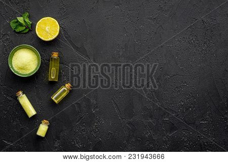 Natural Citrus Cosmetics. Spa Oil Near Lemon On Black Background Top View Mock-up.