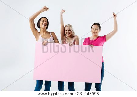 Our Motto. Nice Pleasant Good Looking Women Looking At You And Holding A Poster While Presenting The