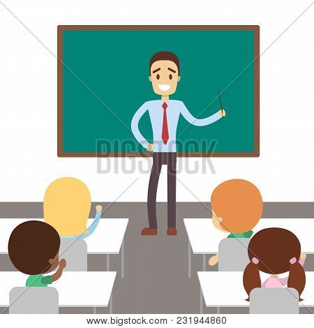 Teacher In Classroom With Pupils Studying And Standing Near The Chalkboard.