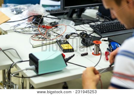 Electrician Soldering Wires. Closeup On Working Place With Many Electronic Equipment.