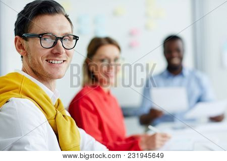 Happy student in eyeglasses and casualwear looking at camera with his groupmates on background