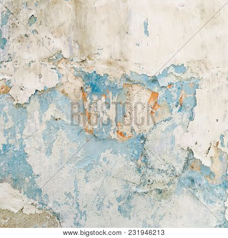 Peeled, weathered and worn out plaster on the wall. A grunge white wall background.