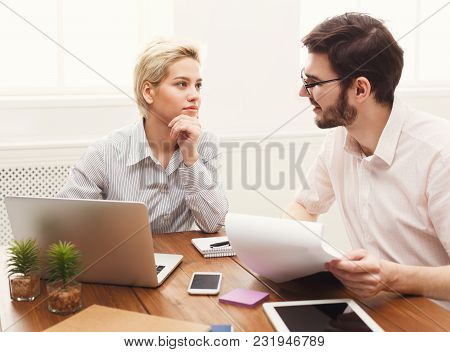 Serious Couple Of Young Colleagues Working In Modern Office. Two Coworkers Discussing Their Work, Wo