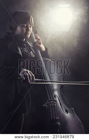 Close-up Of Cellist Playing Classical Music On Cello Against A Black Background. Fog In The Backgrou