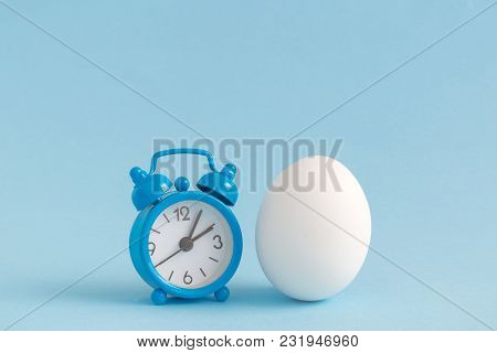 Small Alarm Clock And White Egg On Pastel Blue Background. Eastertime Minimal Concept.