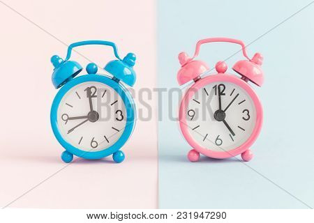Two Small Alarm Clocks On Pastel Blue And Pink Background. Working Hours Minimal Concept.