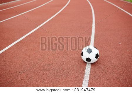 Soccer ball on white line between two race tracks of contemporary stadium