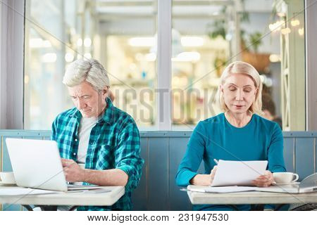 Mature man browsing in the net while analyzing data and aged woman reading financial papers while both sitting in cafe