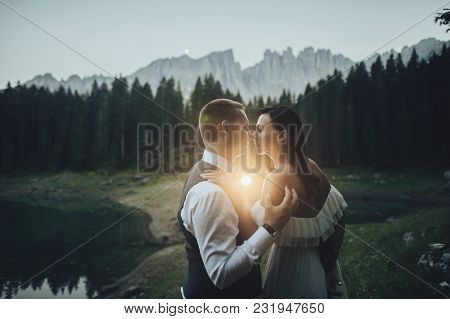 Happy Stylish Couple In Summer Alpine Meadows In Italy. Kissing Bride And Groom
