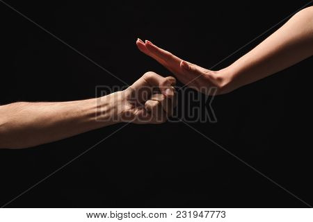 Male Fist Attacing And Female Hand In Defense Against Black Isolated Backgorund. Stop Violence Again