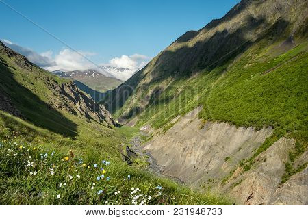 Landscape Of A Mountain Valley With View At Mountain River And Caucasus Mountain Range. Blue Sky Wit