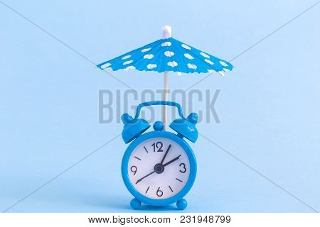 Alarm Clock And Paper Umbrella On Pastel Blue Background. Summer Vacation Minimal Concept.