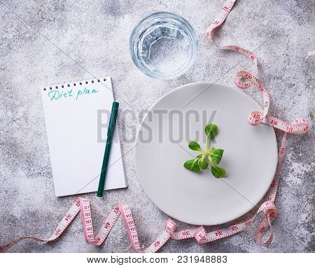 Weigh Loss Concept. Plate With Salad Leaves, Water And Measuring Tape