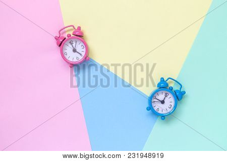 Small Blue And Pink Alarm Clocks On Colorful Pastel Background Flat Lay Creative Minimal Concept.