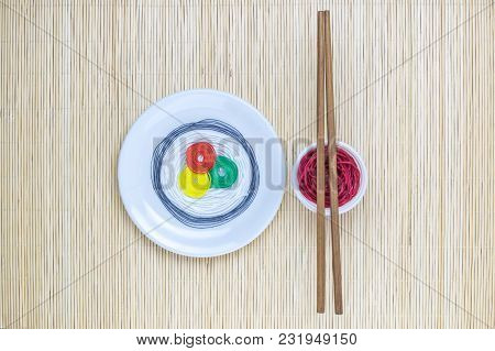Japanese Sushi With Soy Sauce Made From Colorful Threads And Chopsticks On Bamboo Straw Mat Backgrou