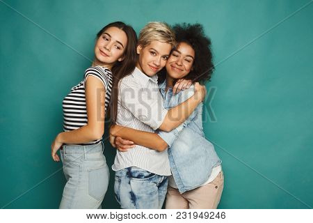 Happy Female Friends Having Fun At Blue Background. Three Young Women Having Friendly Talk, Gossipin