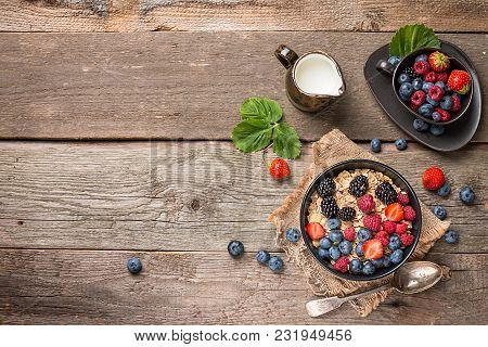 Delicious Homemade Granola Or Oatmeal With Berries For Breakfast Over Rustic Wooden Background, Top