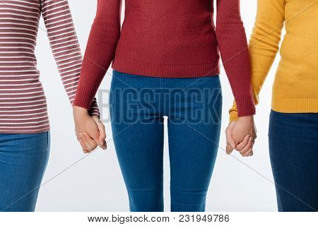 Female Unity. Nice Pleasant Young Woman Standing And Holding Her Friends Hands While Shoeing Their U
